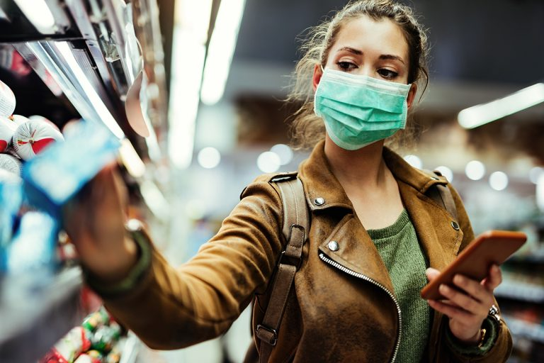 Lady shopping in a supermarket with a protective face mask on, adhering to Covid19 rules