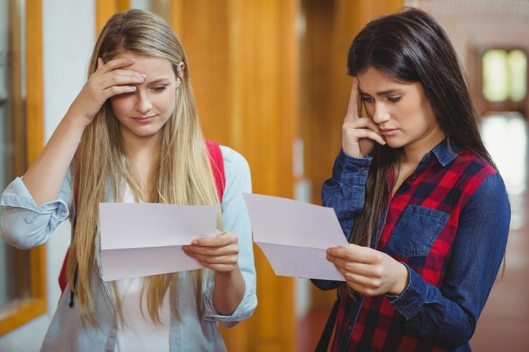 Two young girls at school reading their GCSE results letters looking concerned