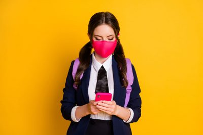 School girl wearing a face mask ready to go back to school, with Covid19 safety measures in place.