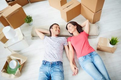 Happy young couple lying on the floor of new house after using Help to Buy scheme