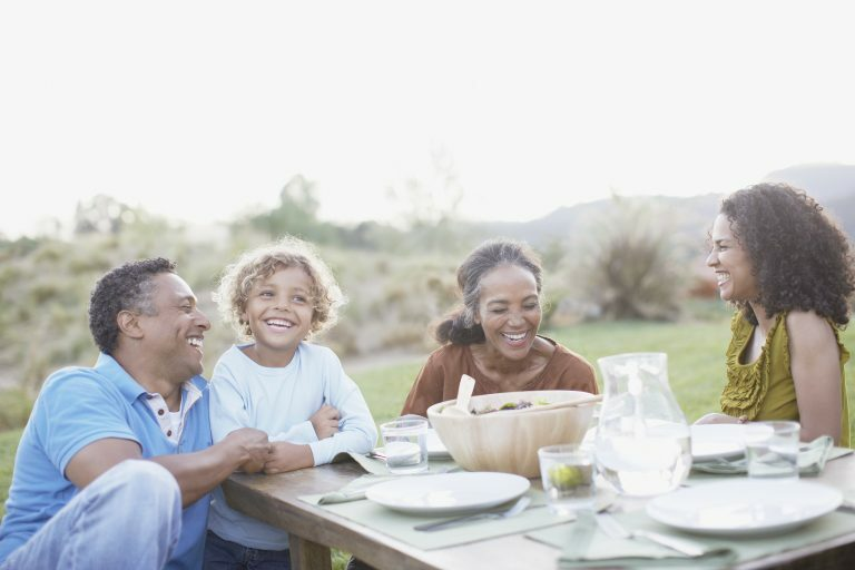 Family enjoying a meal outside on a sunny evening at their holiday home, staycationing