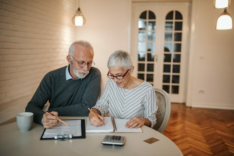 A senior couple taking a closer look at their budget in the comfort of their home, being inticed by risky investments